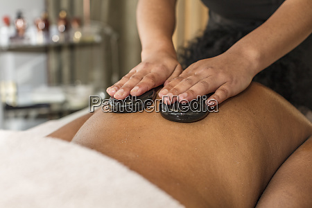 woman receiving a hot stone massage