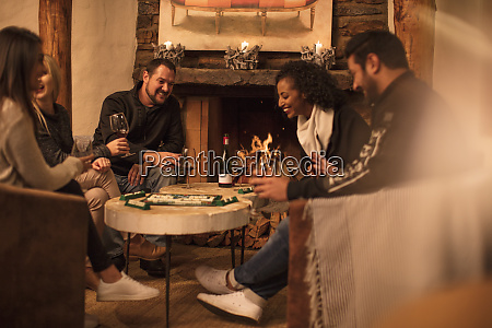 friends sitting together at table playing