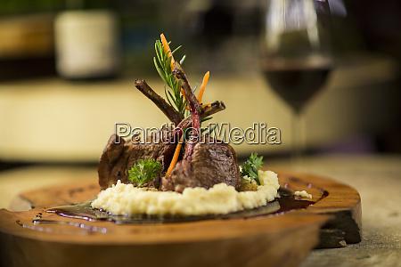 garnished lamb chop on wooden serving