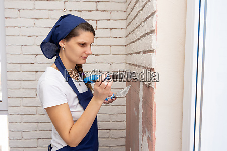 plasterer plasters the wall causing it