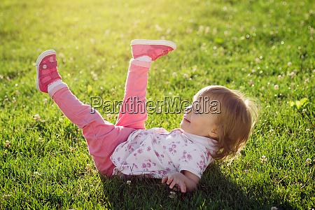 little girl playing on grass