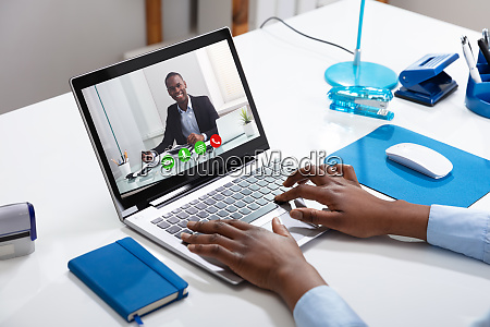 businesspersons videoconferencing with male colleague on