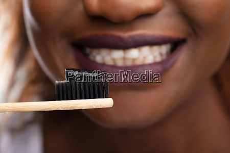 woman holding tooth brush with black