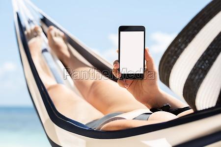 woman lying on hammock using mobile