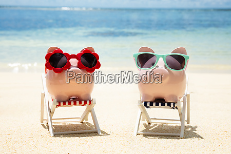 two pink piggybanks with sunglasses on