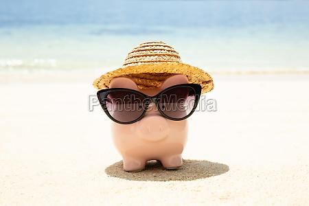 piggybank wearing black sunglasses on beach