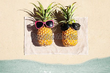 two pineapple lying on towel over