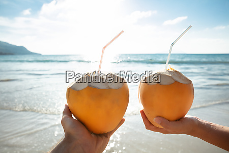 couples hand holding coconut in front