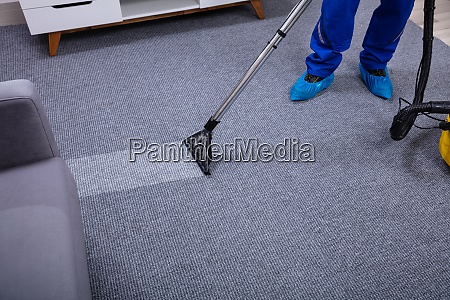 male janitor cleaning carpet