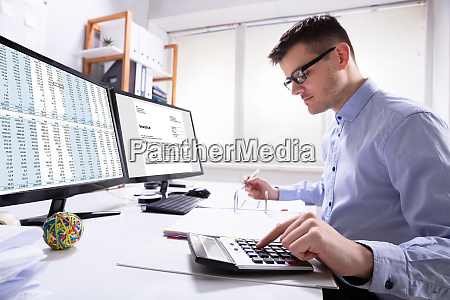 businessman calculating invoice in office