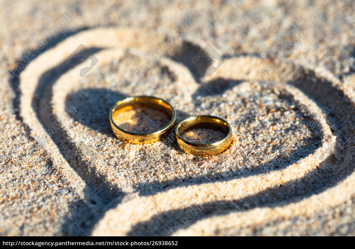 Golden Wedding Rings Inside The Heart Shape On Sand Royalty Free Photo 26938652 Panthermedia Stock Agency