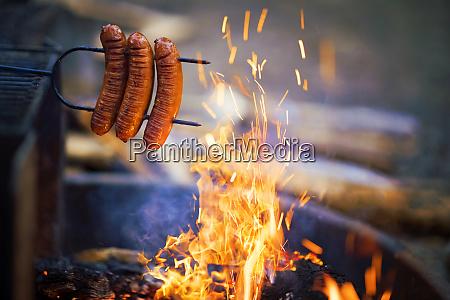 preparing sausage on campfire camping dinner