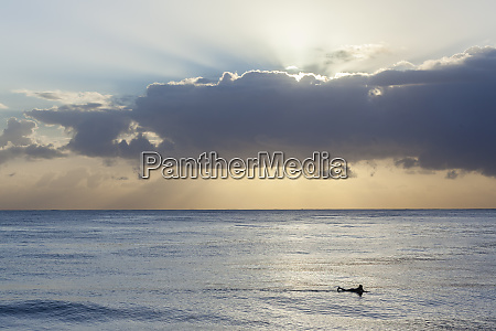 surfer ocean silhouetted horizon dawn