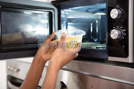human heating food in microwave oven