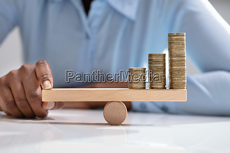 businesswoman balancing stacked coins with finger