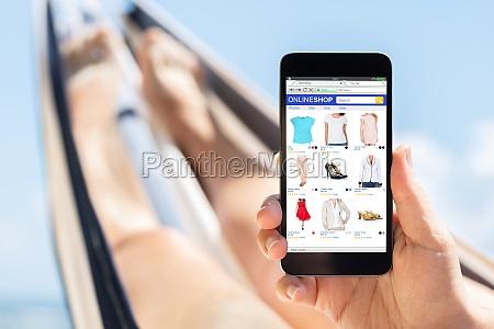 woman lying on hammock shopping online
