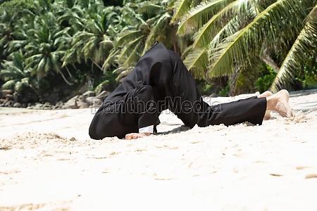 unsuccessful businessman burying his head in
