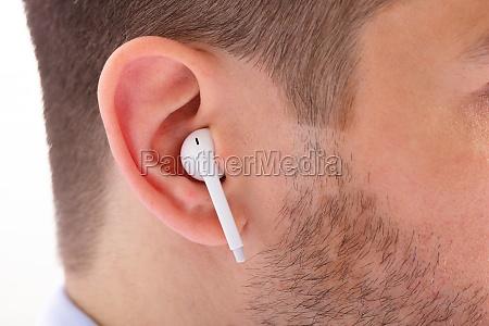 wireless earphone in mans ear