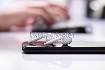 earphone and smartphone on desk