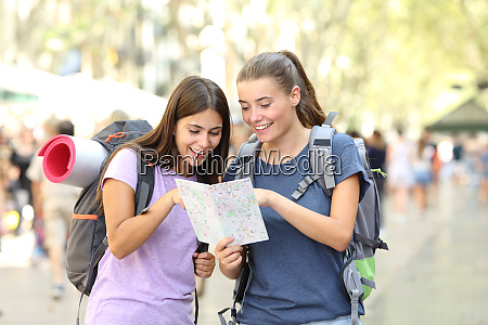 happy backpackers consulting a paper guide