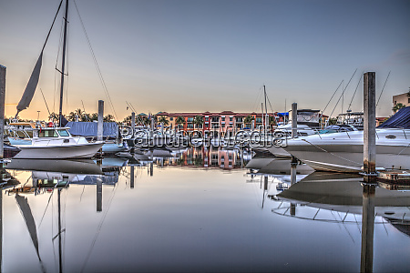 sunrise over a harbor with sailboats