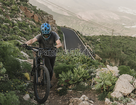 spain lanzarote mountainbiker pushing his bike