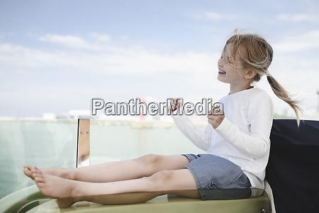 happy little girl sitting on lounger