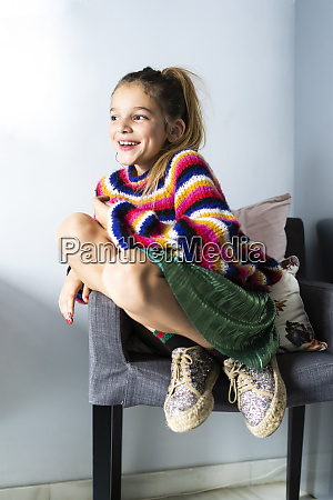 happy girl in striped pullover sitting