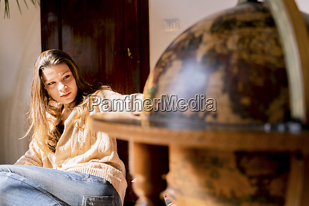 young woman sitting by globe looking