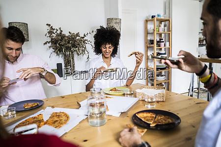 friends having fun eating pizza taking