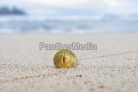bitcoin on a sandy beach