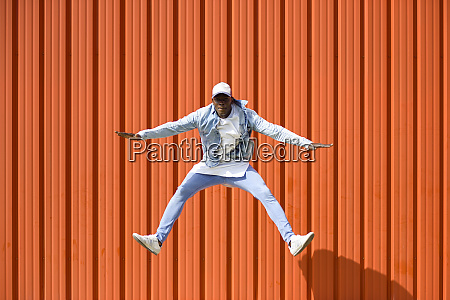 man wearing casual denim clothes jumping