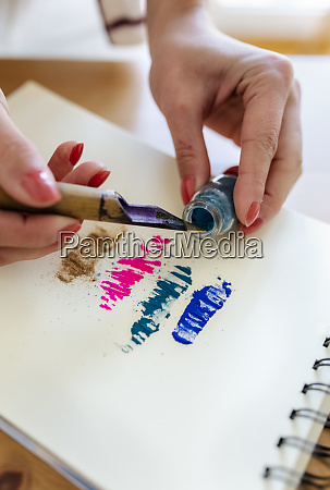 womans hand applying colour pigments at