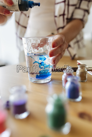 painter filling liquid colour into glass