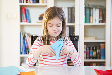 girl tinkering with paper on table