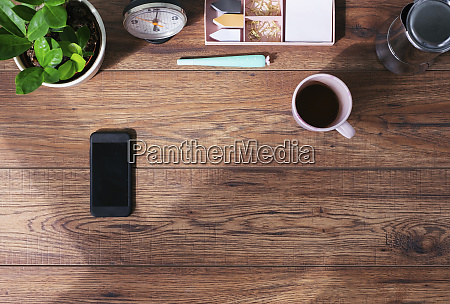 wooden office desk with smartphone and