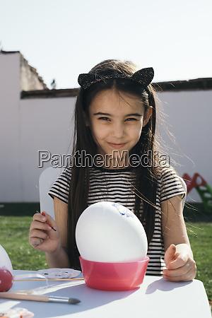 girl painting easter egg in garden