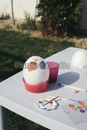 kids painted easter egg in garden