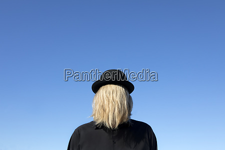 blond hair covering mans face wearing