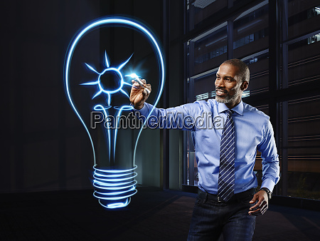 businessman painting lightbulb with a sun