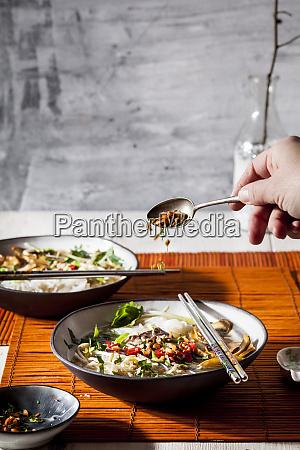 womans hand garnishing vietnamese rice noodle