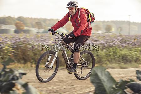 man riding mountainbike on field ath