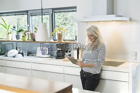 content woman standing in kitchen using