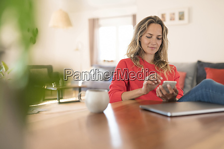 woman using cell phone on dining
