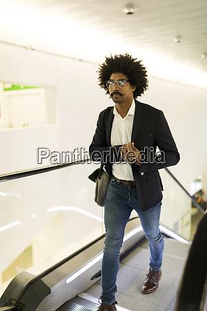 businessman on the move on escalator