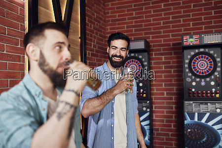 two happy friends drinking beer at
