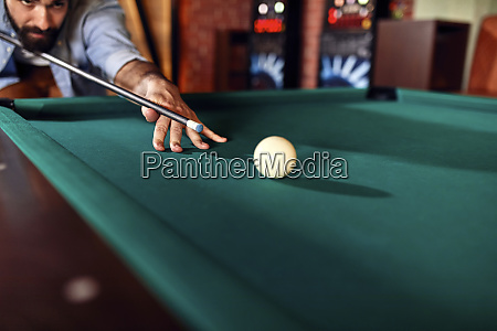 close up of man playing billiards