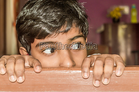 young boy curiously looking outside through