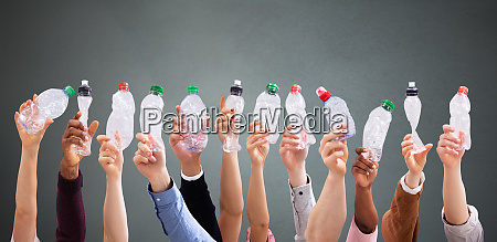 people holding crushed water bottles