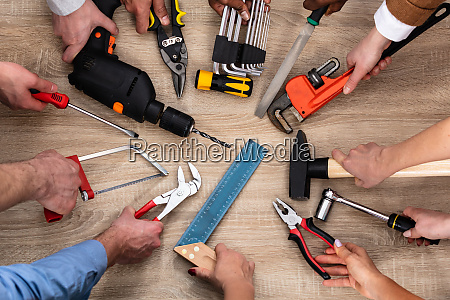 people hand holding carpentry tools